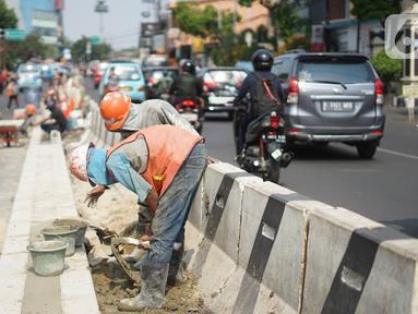Pekerja menyelesaikan pembuatan separator jalan di kawasan Pasar Minggu, Jakarta Selatan, Rabu (23/10/2019). Pembuatan separator permanen tersebut merupakan bagian dari penataan kawasan Pasar Minggu agar lebih tertata dengan rapi. (Liputan6.com/Immanuel Antonius)