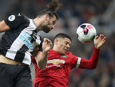Penyerang Newcastle United, Andy Carroll berebut bola dengan pemain Manchester United, Marcos Rojo pada laga pekan kedelapan Premier League, di St James' Park, Minggu (6/10/2019). Manchester United (MU) menelan kekalahan 0-1 dari Newcastle United. (Owen Humphreys/PA via AP)