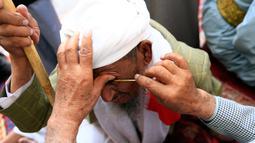 Seorang pria Yaman mengoleskan kosmetik tradisional kohl ke kelopak mata pria lain di Masjid Agung, kota tua Sanaa pada 9 mei 2019. Bagi muslim Yaman, pemakaian kohl diyakini mampu membersihkan dan melindungi mata dari penyakit ini sudah menjadi tradisi setiap bulan Ramadan. (MOHAMMED HUWAIS/AFP)