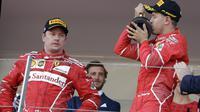 Pebalap Ferrari, Sebastian Vettel merayakan kemenangan sementara Kimi Raikkonen hanya melihatnya dengan tatapan kosong pada F1 GP Monako, (28/5/2017). (AP/Claude Paris)