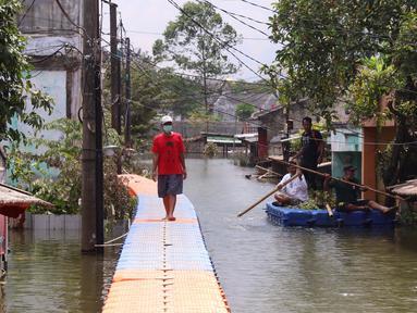 Warga berjalan melintasi jembatan apung saat banjir melanda Perumahan Periuk Damai, Tangerang, Banten, Selasa (23/2/2021). Adanya jembatan apung mempermudah warga saat melintasi banjir setinggi 2,5 meter di tempat tersebut. (Liputan6.com/Angga Yuniar)