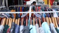 Pengunjung memilih koleksi pakaian di salah satu stand pada gelaran JakCloth di halaman Istora Senayan, Jakarta, Senin (4/6). Beragam merek pakaian anak muda dihadirkan pada gelaran yang berlangsung hingga 10 Juni 2018. (Liputan6.com/Helmi Fithriansyah)