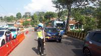 Petugas kepolisian sedang mengurai kendaraan yang melalui jalur Nagreg, Kabupaten Bandung. (Huyogo Simbolon)
