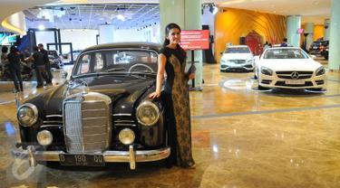 Model berpose di dekat mobil keluaran lama Mercedes Benz di Star Expo 2016,Jakarta, Rabu (23/11). Pameran tersebut merupakan pameran independen pertama dan terbesar bagi Mercedes Benz di Indonesia. (Liputan6.com/Angga Yuniar)
