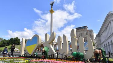 Pekerja menanam bunga di Independence Square menjelang final Liga Champions antara Real Madrid dan Liverpool FC, Kiev, Ukraina, Senin (21/5). Final Liga Champions akan berlangsung pada 26 Mei 2018. (Sergei SUPINSKY/AFP)