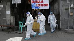 Petugas kesehatan mengenakan pakaian pelindung usai melakukan tes usap pada penduduk desa yang dilockdown untuk mencegah penyebaran COVID-19 di Manila, Filipina, Senin (15/3/2021). Kementerian Kesehatan Filipina melaporkan lonjakan kasus COVID-19 selama lebih dari seminggu. (AP Photo/Aaron Favila)