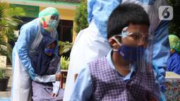Siswa Sekolah Dasar (SD) bersiap untuk imunisasi di SDN Tangerang 1, Kota Tangerang, Kamis (19/11/2020). Pemberian imunisasi tersebut untuk memberikan perlindungan kepada anak-anak usia SD serta meningkat daya tahan tubuh serta mencegah berbagai penyakit. (Liputan6.com/Angga Yuniar)