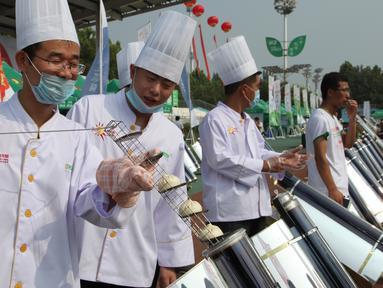 Para koki memasak roti menggunakan tabung logam dan kaca yang dipanaskan oleh cermin melengkung untuk menangkap sinar matahari di Dezhou, Shandong Timur, Cina, 2 Agustus 2018. Koki memasak dengan kompor tenaga surya. (AP Foto/Fu Ting)