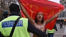 Petugas menghalau aktivis wanita gerakan hak perempuan Femen saat unjuk rasa memperingati 100 tahun Revolusi Bolshevik di pusat kota Kiev, Ukraina (7/11). (AFP Photo/Genya Savilov)