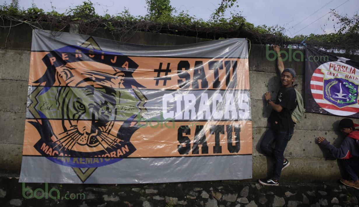Dua Orang Suporter The Jack memasang spanduk dekat Lapangan Youth Training Center, Sawanngan, Depok, Rabu (17/2/2016). (Bola.com/Nicklas Hanoatubun)