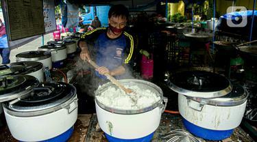Petugas Taruna Siaga Bencana (Tagana) memasak nasi di Dapur Umum Kementerian Sosial di GOR Otista, Jakarta, Minggu (21/2/2021). Dalam sehari, petugas menyiapkan hingga 6.000 paket nasi kotak yang didistribusikan ke 11 kelurahan terdampak banjir. (Liputan6.com/Faizal Fanani)