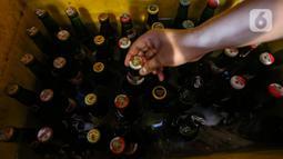 Pekerja mengambil botol minuman keras atau miras dari wadah penyimpanan di kafe kawasan Jakarta Selatan, Selasa (2/3/2021). Aturan yang diteken oleh Presiden Joko Widodo pada 2 Februari 2021 terkait memperbolehkan masyarakat untuk berinvestasi di produk miras dicabut. (Liputan6.com/Johan Tallo)