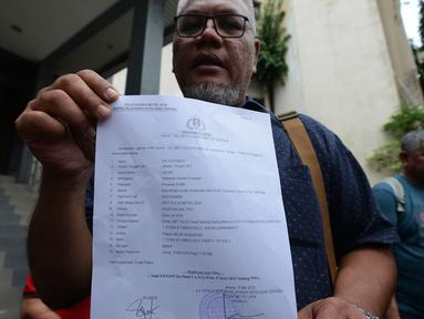 Perwakilan warga dari kasus penipuan perjalanan Travel Agent Hidup Makmur Tentram (HMT) menunjukkan surat laporan di Polda Metro  Jaya, Jakarta, Jumat (10/5). Ratusan orang jemaat batal berangkat ke Yerusalem hingga saat ini belum ada kejelasan untuk berangkat. (merdeka.com/Imam Buhori)
