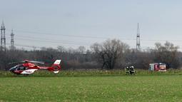 Polisi dan regu penyelamat mengamankan area lokasi terjadinya kecelakaan udara antara pesawat kecil dengan helikopter di Philippsburg, Jerman, Selasa (23/1). Puing-puing dua badan pesawat udara jatuh dalam wilayah yang cukup luas  (Rene Priebe/dpa via AP)