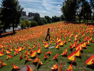Seorang perempuan berjalan di antara bendera Spanyol untuk mengenang korban COVID-19 di Madrid, Minggu (27/9/2020). Asosiasi keluarga korban virus corona memasang 53.000 bendera kecil Spanyol di sebuah taman Madrid untuk menghormati mereka yang meninggal akibat pandemi. (AP Photo/Manu Fernandez)