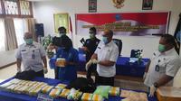 Kurir sabu dari sindikat narkoba internasional memegang barang bukti narkoba yang disita Badan Narkotika Nasional Provinsi Riau. (Liputan6.com/M Syukur)